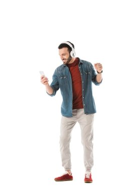 happy handsome man listening music in headphones and using smartphone isolated on white