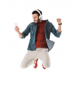Excited man in headphones jumping while using smartphone and showing yes gesture isolated on white stock vector