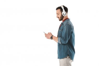 side view of handsome man in headphones using smartphone isolated on white