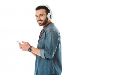 smiling man in headphones using smartphone and looking at camera isolated on white