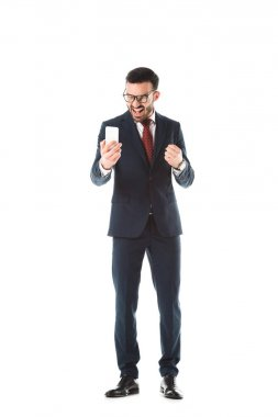 irritated businessman screaming and showing fist while having video call on smartphone isolated on white