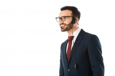 handsome call center operator in headset smiling and looking away isolated on white