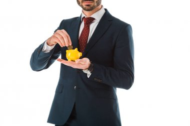 cropped view of businessman putting coin into piggy bank isolated on white