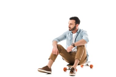 Pensive bearded man sitting on longboard and looking away isolated on white stock vector