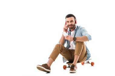 cheerful man in headphones talking on smartphone while sitting on longboard isolated on white
