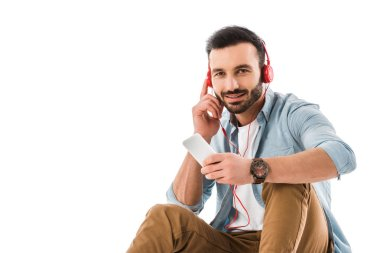 handsome smilng man in head phones using smartphone and looking at camera isolated on white
