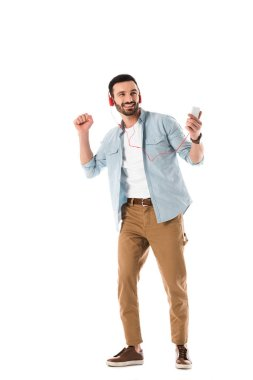 happy man in headphones listening music and holding smartphone while dancing isolated on white