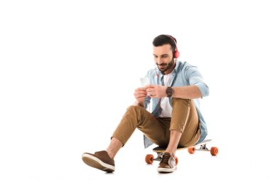 handsome smiling man listening music in headphones while sitting on longboard and using smartphone isolated on white