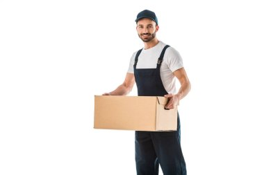 Handsome delivery man in overalls holding cardboard box and smiling at camera isolated on white stock vector
