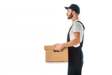 Side view of delivery man in overalls and cap holding cardboard box isolated on white stock vector