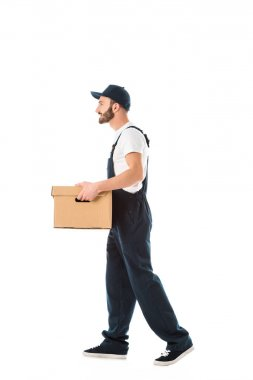 side view of smiling delivery man in overalls carrying cardboard box isolated on white