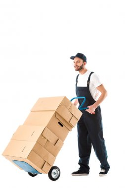 cheerful handsome delivery man transporting cardboard boxes loaded on hand truck isolated on white