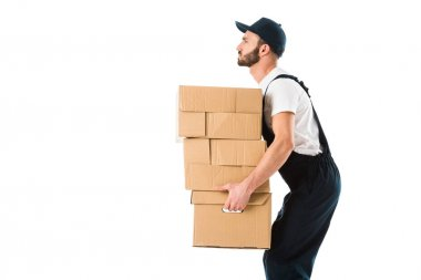 side view of serious delivery man carrying cardboard boxes isolated on white