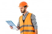 Fotografie serious construction worker in safety vest and helmet looking at clipboard isolated on white