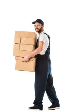 cheerful delivery man carrying cardboard boxes and looking at camera isolated on white