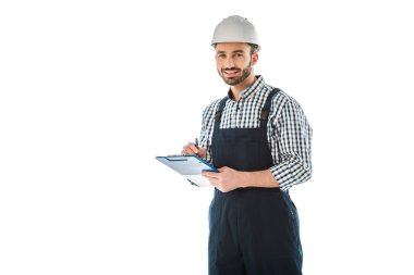 smiling construction worker writing on clipboard and looking at camera isolated on white