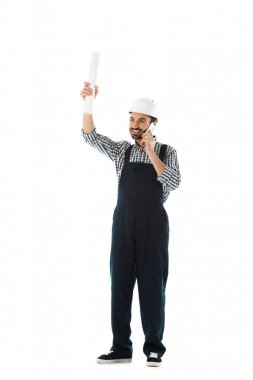 cheerful construction worker talking on smartphone while holding rolled paper in raised hand isolated on white