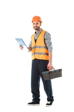 cheerful construction worker holding toolbox and clipboard isolated on white
