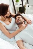 krásná žena, která se dívá na šťastného muže ležet na posteli v bílém tričku