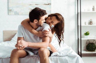 Cheerful young woman hugging handsome boyfriend in bedroom stock vector