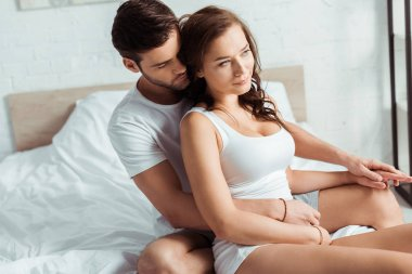 handsome man hugging attractive girlfriend in bedroom