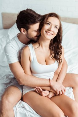 handsome man hugging happy girlfriend in bedroom