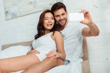selective focus of happy man taking selfie with girlfriend showing tongue in bedroom