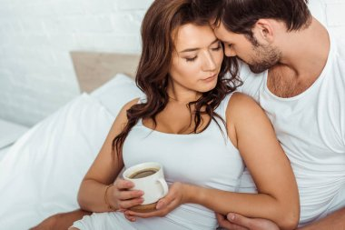 handsome man near attractive woman holding cup of coffee in bed