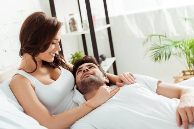 happy girlfriend looking at boyfriend lying on bed