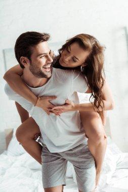 happy man piggybacking attractive girlfriend in bedroom