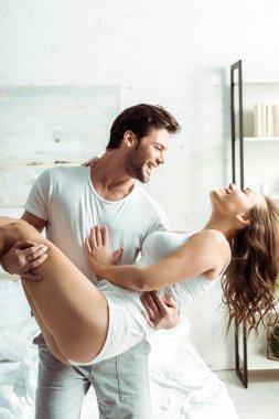 happy boyfriend holding in arms beautiful girlfriend in bedroom