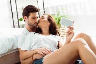 Attractive girl kissing cheek of man while taking selfie on smartphone stock vector
