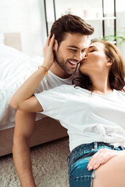 Girlfriend kissing cheek of happy boyfriend in bedroom stock vector