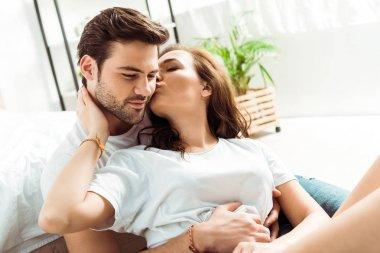 attractive girl kissing cheek of handsome boyfriend in bedroom