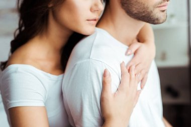 cropped view of woman embracing boyfriend at home