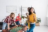 Boldog és mosolygós többnemzetiségű férfiak és nők játszanak asztalifoci nappaliban otthon