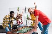 Boldog multikulturális barátok iszik sört, ünneplő és játék asztali foci a nappaliban