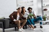 Veselý multikulturní muž opékání s africkou americkou dívkou v obývacím pokoji