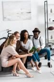 vidám multikulturális férfiak pirítás a boldog nők a nappaliban