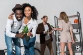szelektív középpontjában afro-amerikai férfi és lány gazdaság üveg sört, és mosolyogva barátok közelében