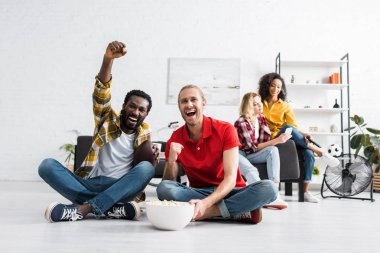Happy and positive multicultural young people sitting on floor and watching sport game with bowl of popcorn