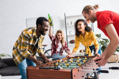 Four happy and joyful multiethnic friends playing table football in living room