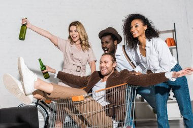 cheerful man riding in shopping cart and holding bottle near multicultural friends