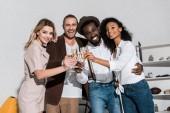 kis látószögű nézet vidám multikulturális barátok mosolyogva, miközben csengő pezsgő szemüveg