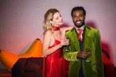vidám és vonzó nő piros ruhában nézett szép afro-amerikai férfi pezsgő üveg