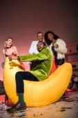 alacsony látószögű tekintettel vidám afro-amerikai ember ül a bab rossz szék közelében boldog barátok