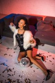 attractive african american girl holding champagne glass while sitting on floor near confetti