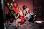 selective focus of cheerful blonde girl in red dress holding balloons and champagne glass near multicultural friends
