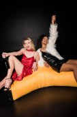 excited blonde girl sitting on bean big chair with african american friend holding champagne glass on black