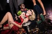 boldog lány piros ruhában gazdaság üveg pezsgő közelében afro-amerikai ember és barátai fekete